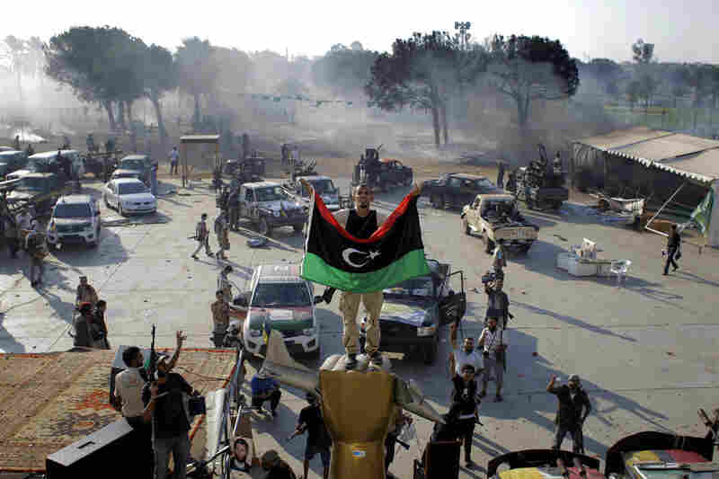 A Libyan rebel stands on a monument in Gadhafi's main compound.