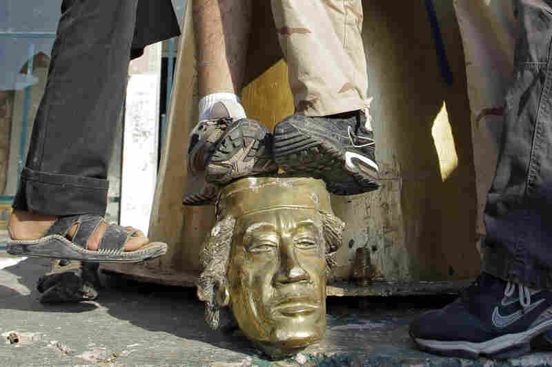 Rebel fighters trample the head of a Gadhafi statue in his compound.