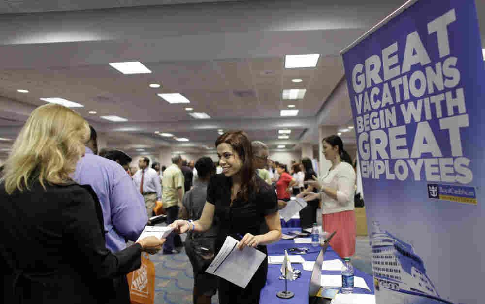 A Royal Caribbean recruiter (c) hands out an application at a Congressional Black Caucus jobs fair in Miami, Aug. 23, 2011.