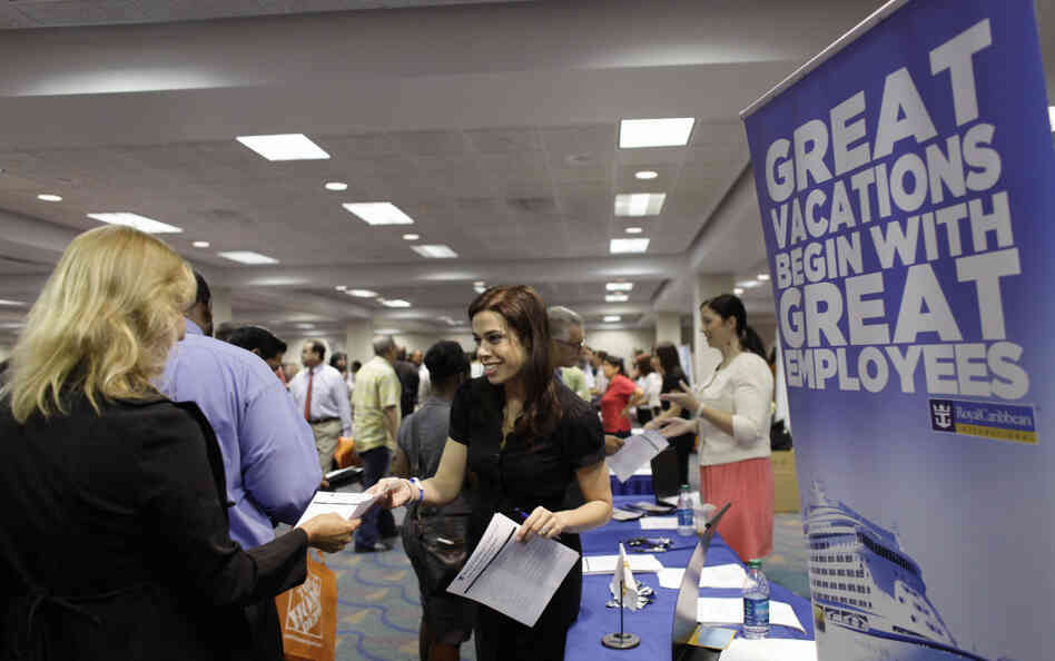 A Royal Caribbean recruiter (c) hands out an application at a Congressional Black Caucus jobs fair in Miami, Aug. 23, 2011.