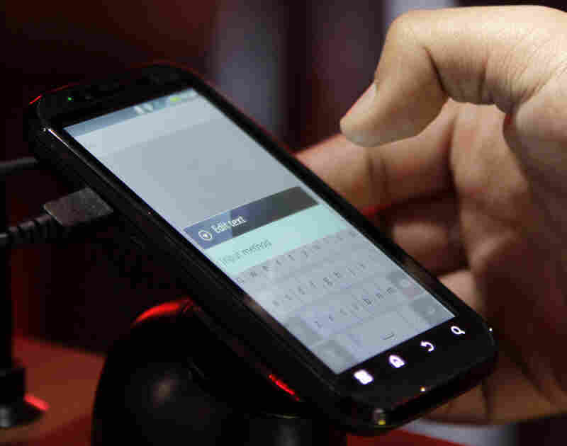 A buyer tests a Motorola Droid phone in this photo from January. Google purchased Motorola for $12.5 billion, gearing up in a patent war that has seen corporations try to pummel their competitors.