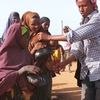 Women and children at the Dadaab refugee complex in Kenya line up Aug. 24 to  receive iftar — a meal of rice, meat and vegetables to break  the Ramadan fast. Somalis are fleeing across the border to Kenya to escape  extreme poverty associated with the country's severe drought, famine and an  Islamist insurgency.