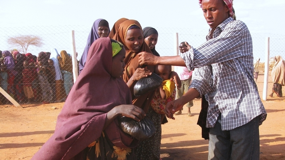 Women and children at the Dadaab refugee complex in Kenya line up Aug. 24 to  receive iftar — a meal of rice, meat and vegetables to break  the Ramadan fast. Somalis are fleeing across the border to Kenya to escape  extreme poverty associated with the country's severe drought, famine and an  Islamist insurgency. (NPR)