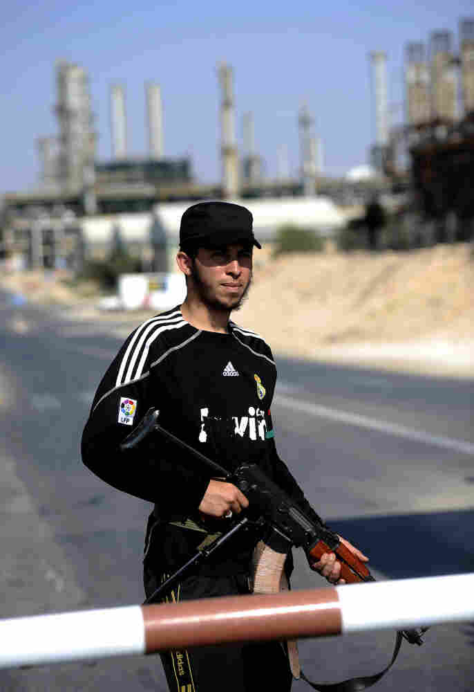 A Libyan rebel stands guard at the entrance to the Zawiya oil refinery, about 30 miles west of Tripoli, on Aug. 19. Rebels have taken complete control of the key oil refinery. Before the conflict, Libya supplied 2 percent of the world's oil, but restarting oil field operations won't be a simple task.