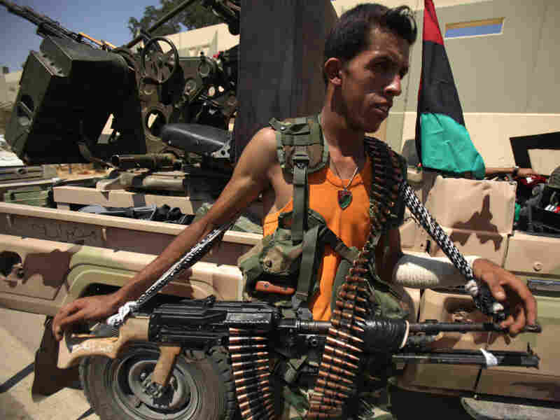 A Libyan rebel stands with his weapon at the Bab al-Aziziya compound in Tripoli a day after it was captured by rebel forces.