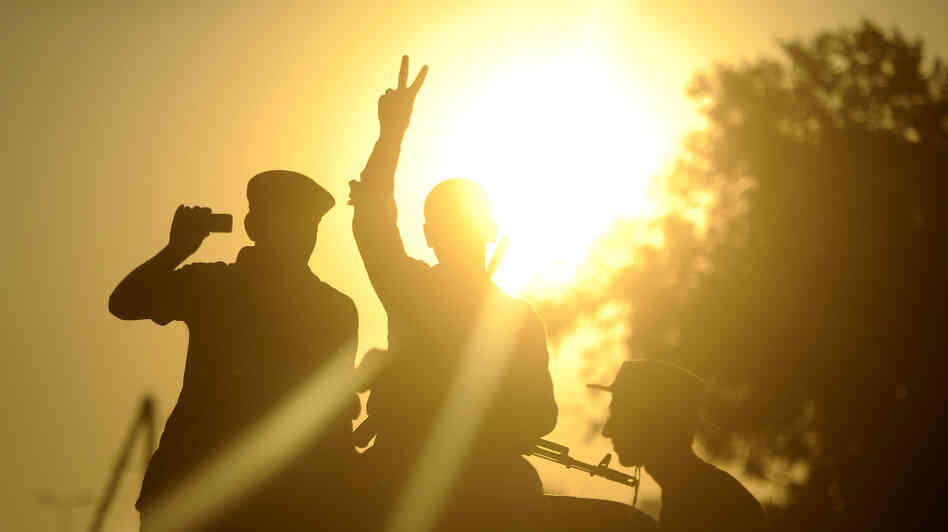 Opposition fighters flashed the V-sign for victory during celebrations in Tripoli's newly named Martyrs Square, formerly known as Green Square, on Tuesday (Aug. 23, 2011).