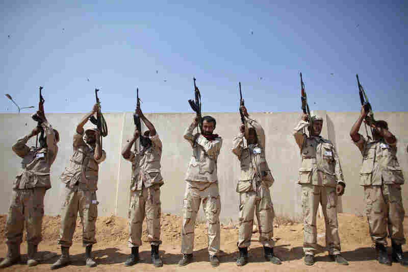 Rebel fighters shoot to the sky during a funeral in Benghazi.