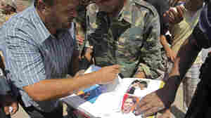 On Wednesday, opposition fighters looked through an album they found inside Moammar Gadhafi's compound in Tripoli. It includes photos of former Secretary of State Condoleezza Rice.