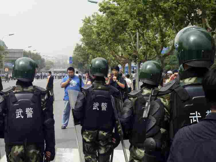 Chinese paramilitary police stand guard as hundreds of people protest against the Fujia chemical plant in Dalian, in northeast China's Liaoning province on Aug. 14, 2011. Authorities ordered the shutdown of a chemical plant  as thousands of protesters demanded the factory be moved over pollution fears.