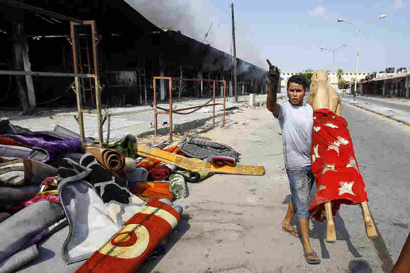 After an intense battle in the Abu Salim district of Tripoli, a man removes a mannequin from a clothes shop.