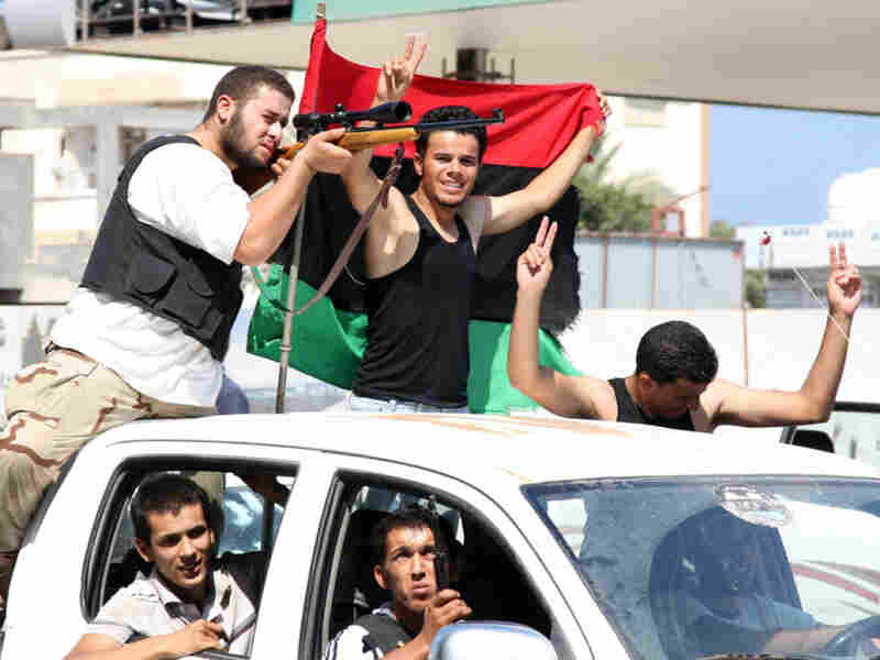 Rebel fighters celebrate their gains in Tripoli on Friday.