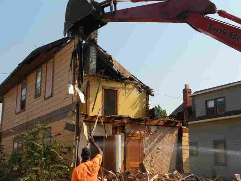 LaMont Rump of Fez Enterprises guides an excavator during the demolition of a house in Cleveland.