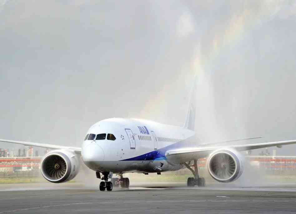 A Boeing 787 Dreamliner arrives at Tokyo's Haneda airport as fire engines spray it with water during a test flight.