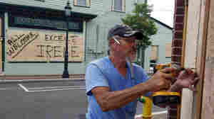 Marvin Hardy drives screws into a sheet of plywood on Washington Mall in Cape May, N.J., on Friday, as he  boards up storefronts in preparation for Hurricane Irene. Mandatory evacuations were under way  affecting nearly 1 million residents and visitors in Cape May County, coastal Atlantic County and Long Beach Island, N.J.