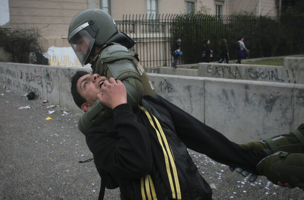 Riot police detain a demonstrator on the second day of a national strike in Santiago, Chile on Thursday.