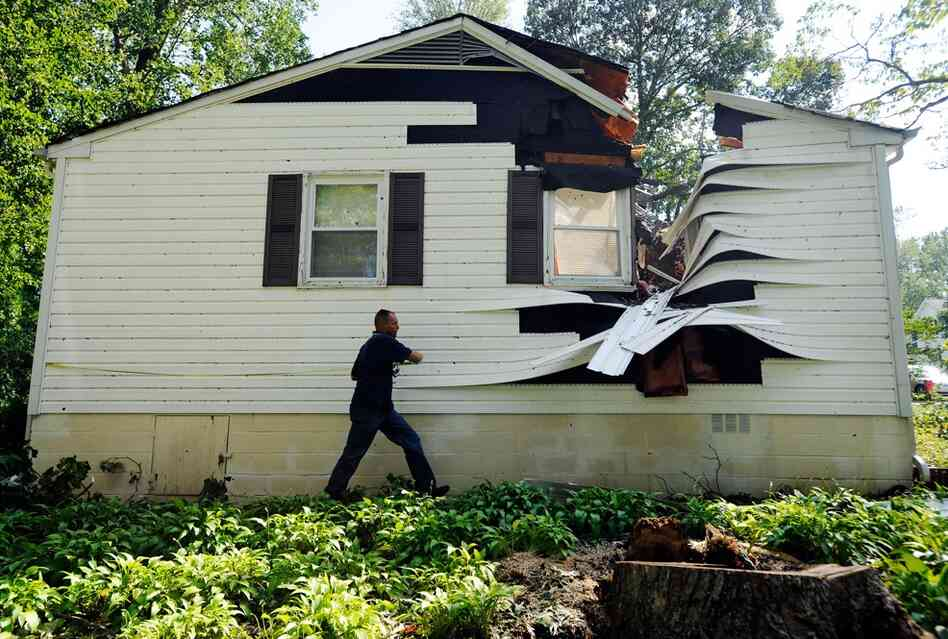 Darrell Tarte surveys damage from a tree at a home hit by the hurricane on Sunday in Port Republic, Md.