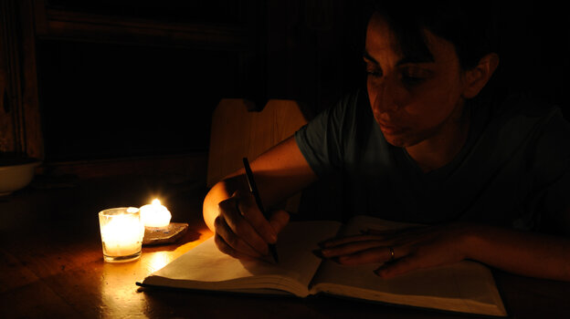 A woman writes in a journal by candlelight.
