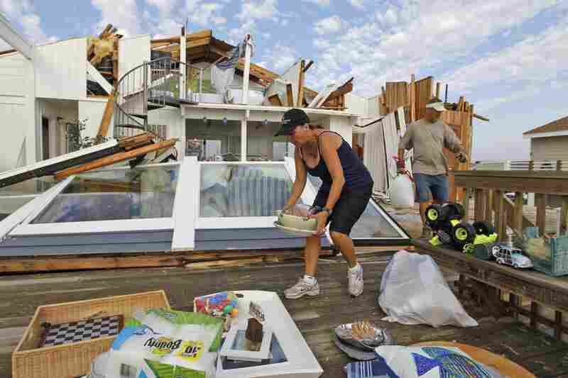 Denise Robinson and Rich Brown clear out belongings from Robinson's storm-damaged beach home in the Sandbridge area of Virginia Beach, Va.