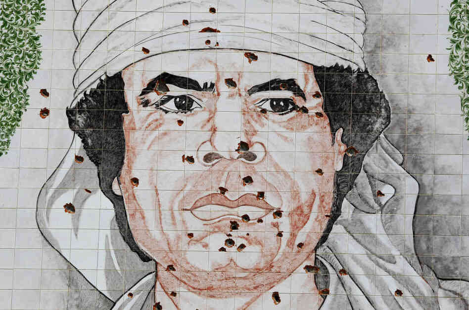A bullet-riddled mural portrait of Moammar Gadhafi sits on a wall in Tripoli. Libyan rebels are looking for the former leader, aided by foreign intelligence services and U.S. spy drones.