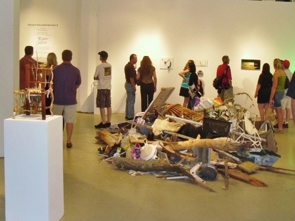 A crowd previews a selection of art from the Reclamation Project, which has reused debris from the tornado in Joplin, Mo.