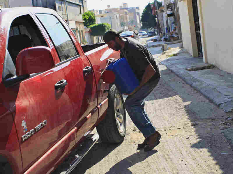 A man pours gas into the tank of his car in Tripoli on Saturday. Residents in the Libyan capital are scrambling to get basic supplies, such as fuel and water.