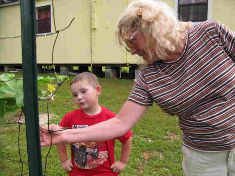 Pamela Landry and her grandnephew, Jason, pick tomatoes in the backyard of her shotgun house. She stayed in Picayune, Miss., after Katrina in part because of her family roots in the area.