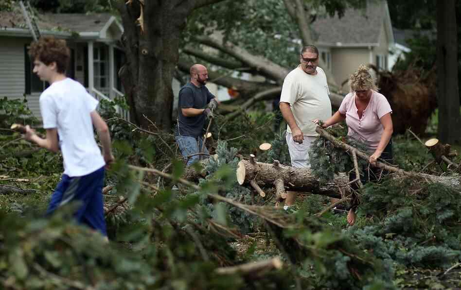 Residents clear debris from downed trees after a tornado spawned by Hurricane Irene touched down, on Sunday in Lewes, Del.