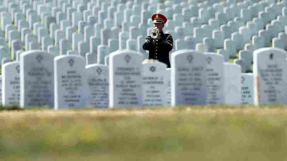 A bugler plays taps during an Aug. 9 funeral at Arlington National Cemetery in Arlington, Va. After reports revealed mishandling of remains at the cemetery, military officials are now working to reconcile the burial records of the 330,000 people laid to rest there.