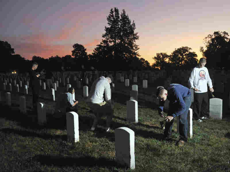 The sun rises over Section 15 at Arlington National Cemetery as soldiers from the Army Old Guard photograph headstones on Aug. 24. Their work is part of a task force to photograph and catalog nearly 220,000 grave markers and the columbarium niches of more than 43,000 sets of cremated remains at Arlington.
