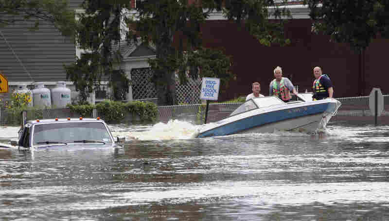 A motorboat passes a submerged pickup truck on Main Street in Washingtonville,