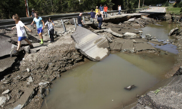 People walk along a washed out section of Route 12 on Monday in Berlin, Vt.