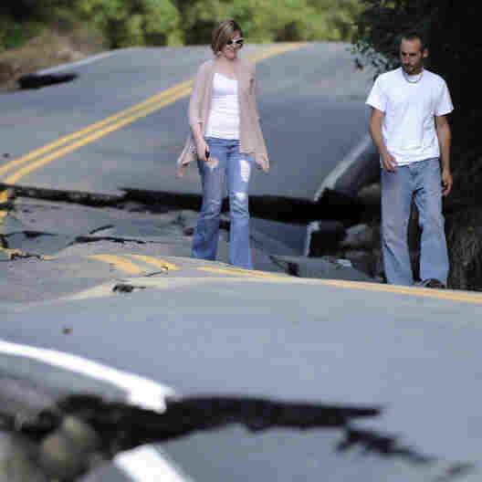 Jarrid Gonyea and his wife, Michelle, check out damage caused by Tropical Storm Irene on Hurricane Road in Keene, N.Y., on Monday. The costs of the storm that stretched across the Eastern Seaboard are estimated to be in the billions.