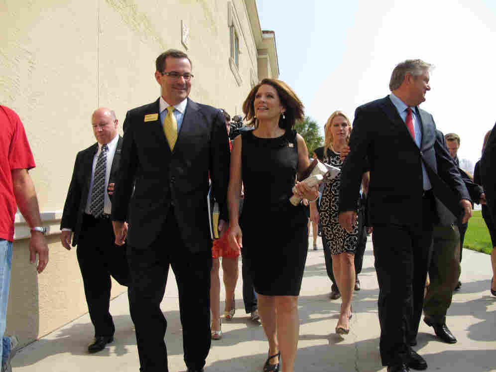 Rep. Michele Bachmann arrives at Idlewild Baptist Church in Lutz, Fla. with Pastor Brian McDougall, next to her and her husband Marcus (r), Sunday, Aug. 28, 2011.