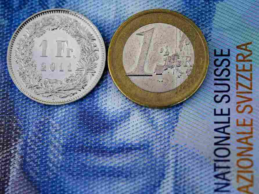 """A """"one Swiss franc coin"""" and a one Euro coin are seen on the top of a 100 Swiss francs note."""