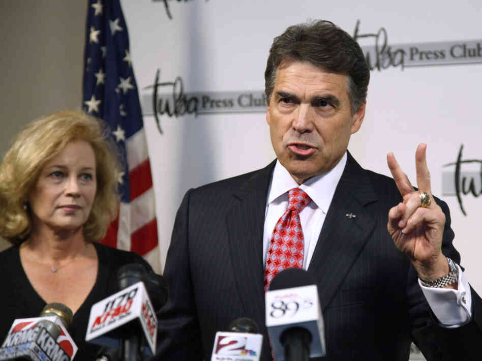 Texas Gov. Rick Perry, with wife Anita, gestures as he answers a question at a news conference in Tulsa, Okla., Monday, Aug. 29, 2011.
