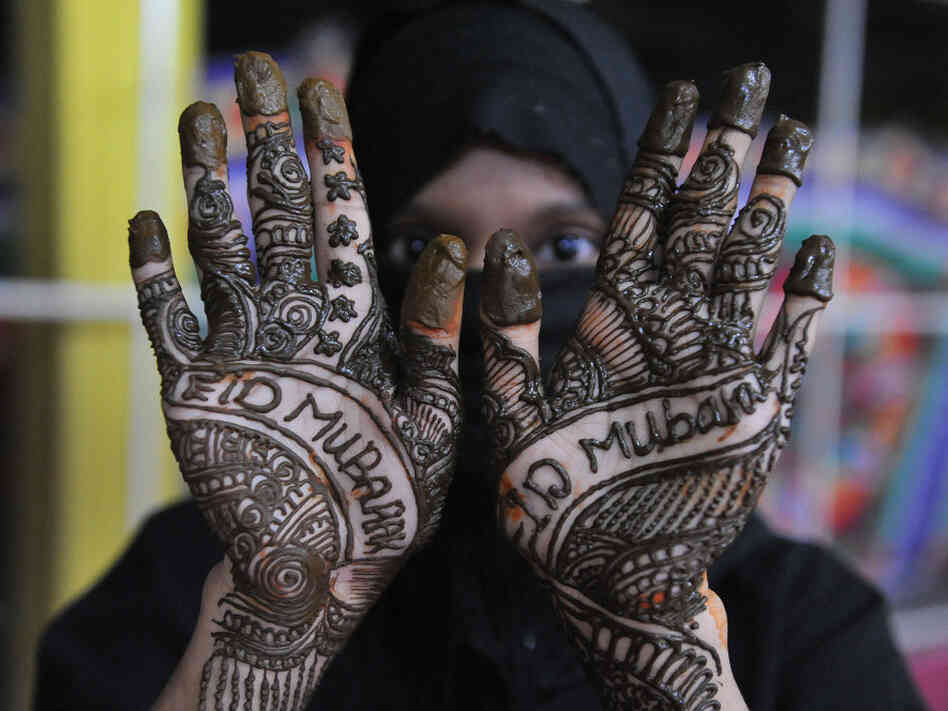 An Indian Muslim woman poses showing her hands decorated with mehendi (henna) during 'Chand Raat' or 'Night of the Moon' in Hyderabad on August 30, 2011, traditionally held on the eve of the festival of Eid al-Fitr.