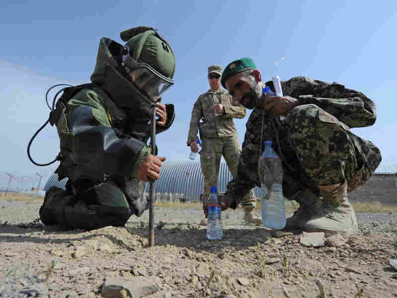 Supervised by U.S. soldiers, Afghan national army personnel participate in a training exercise simulating detonation of an IED near Camp Clark in Afghanistan's Khost province, July 6.