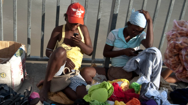 Two women check their cellphones as they hawk their wares on a bridge over the Artibonite River, whose waters are  believed to be the source of Haiti's 2010 cholera outbreak. (AFP/Getty Images)
