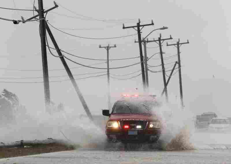 An Oak Bluffs, Mass., fire department vehicle drives through strong winds and ocean spray from the tropical storm while driving along a costal road in Edgartown on Martha's Vineyard on Sunday.