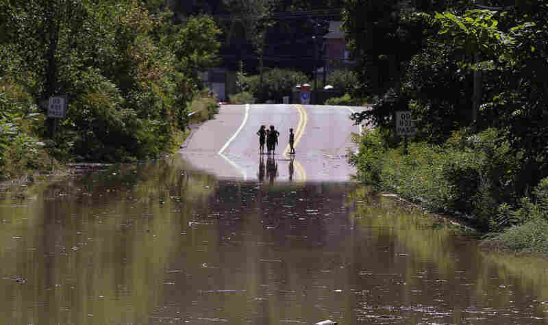 Children stand on the far side of a flooded portion of Route 5, which is closed to traffic, in Northhampton, Mass., on Monday.
