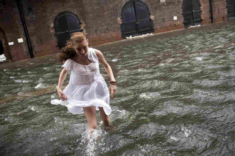 Betty Walsh crosses a flooded street in the Red Hook neighborhood of Brooklyn on Sunday.