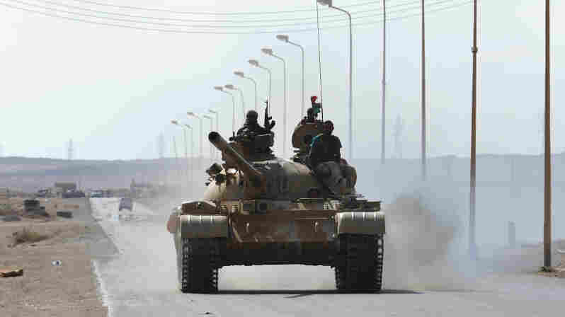Libyan rebel fighters advance in their tank about 60 miles east of the town of Sirte on Tuesday. Sirte is Moammar Gadhafi's hometown and the last bastion of his loyalist forces.