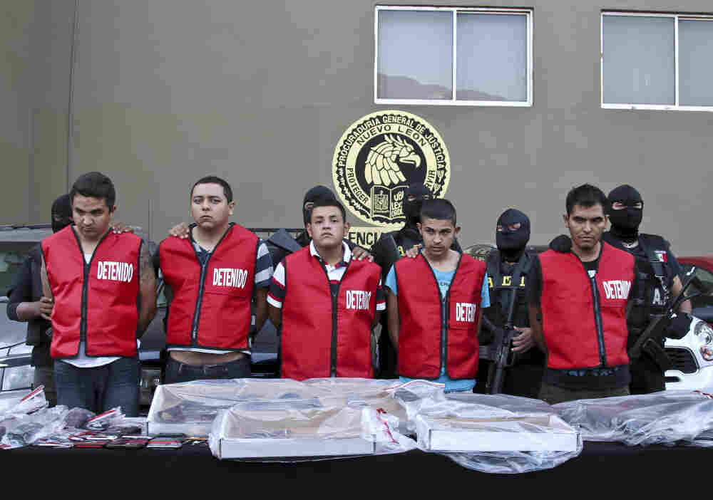 Police officers escort five alleged members of the Zetas drug cartel during their presentation to the press in Monterrey, Mexico on Tuesday.