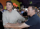 Republican presidential hopeful Texas Gov. Rick Perry (left) shakes hands with a supporter as he goes onstage at the Polk County GOP summer picnic event held at the Iowa State Fairgrounds in Des Moines on Saturday.