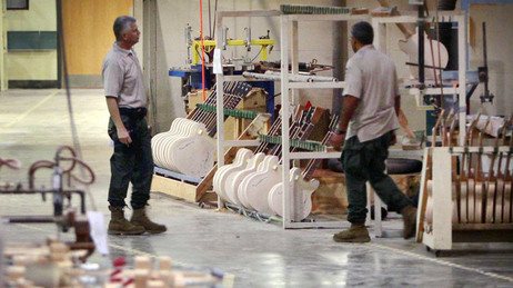 Federal investigators look through the workshop at the Gibson Guitar factory during a raid on the Memphis facility last week.