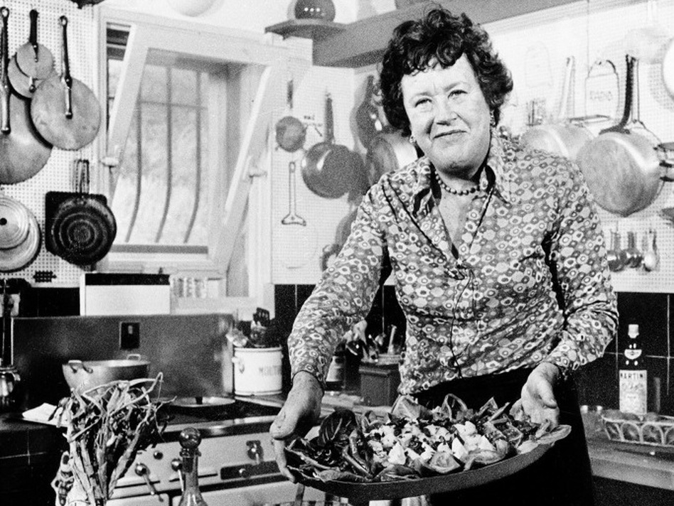 "Bon Appetit: Chef Julia Child shows off a salade nicoise she prepared in the kitchen of her vacation home in southern France, in August 1978. Child remembered the first French dinner she had, back in 1948: sole with mushroom and white wine sauce, and oysters on the half shell. ""I just couldn't get over it,"" she told Terry Gross. ""I hadn't ever had that kind of food."" (AP)"
