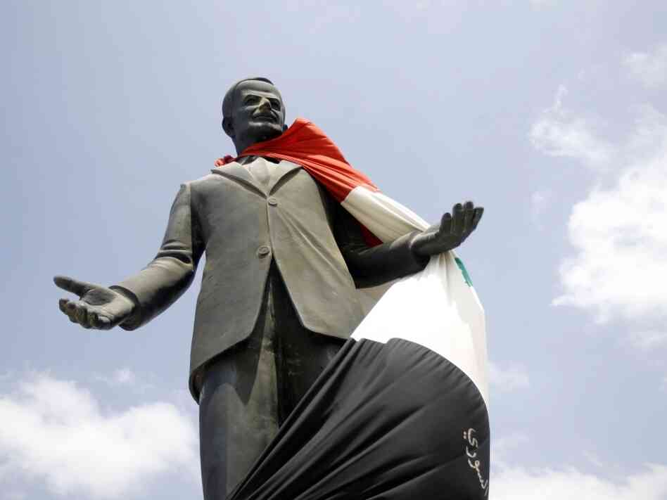 A national flag hangs on a statue of Syria's late president Hafez Assad at the entrance of the city of Homs on Aug. 30, 2011. Rights activists reported widespread anti-regime protests across Syria.