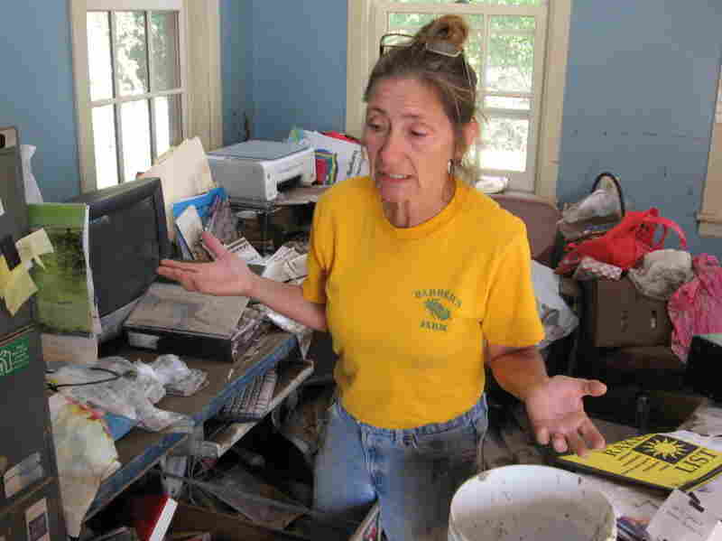 Cindy Barber, in the office of her flooded house, decides what to salvage and what to toss.