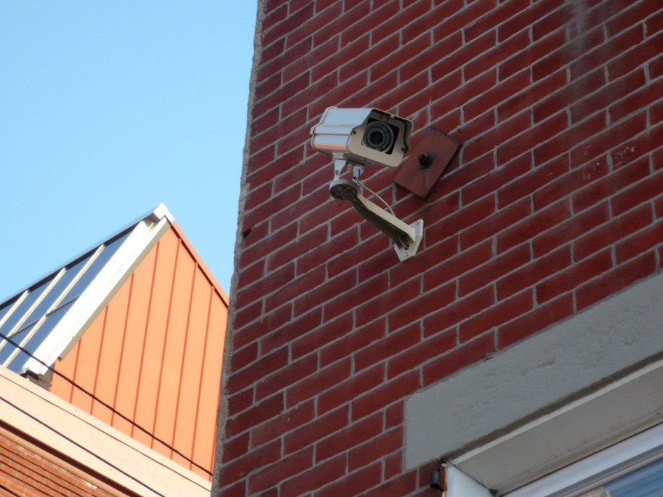 A camera is mounted on a building near Temple University in Philadelphia. Humberto Fernandini, with the company that owns the building, says the owners plan to register their cameras for the police department's new program.