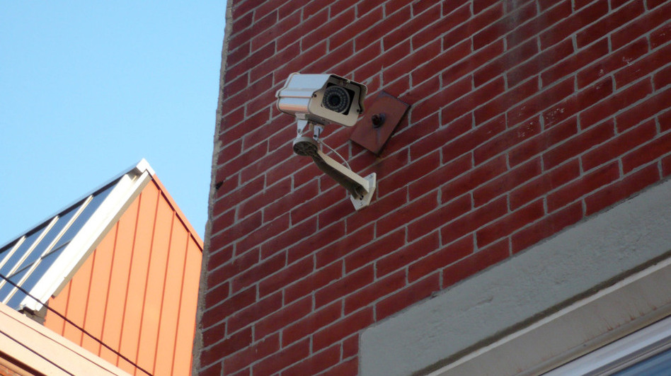 A camera is mounted on a building near Temple University in Philadelphia. Humberto Fernandini, with the company that owns the building, says the owners plan to register their cameras for the police department's new program. (Elizabeth Fiedler for NPR)